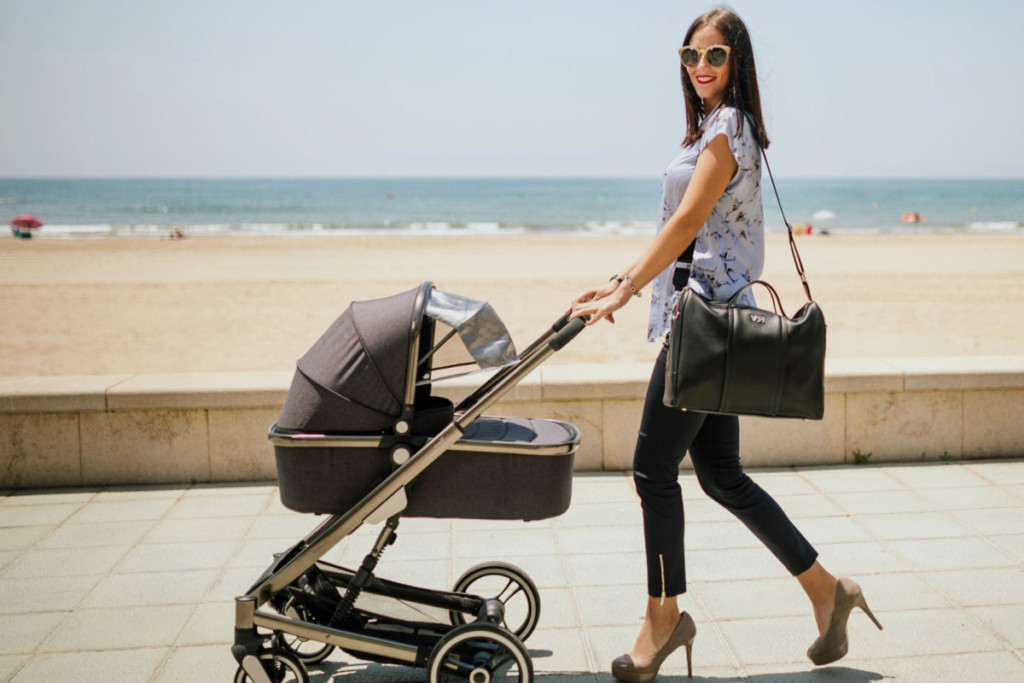 Mujer con un carro de bebé con mosquitera