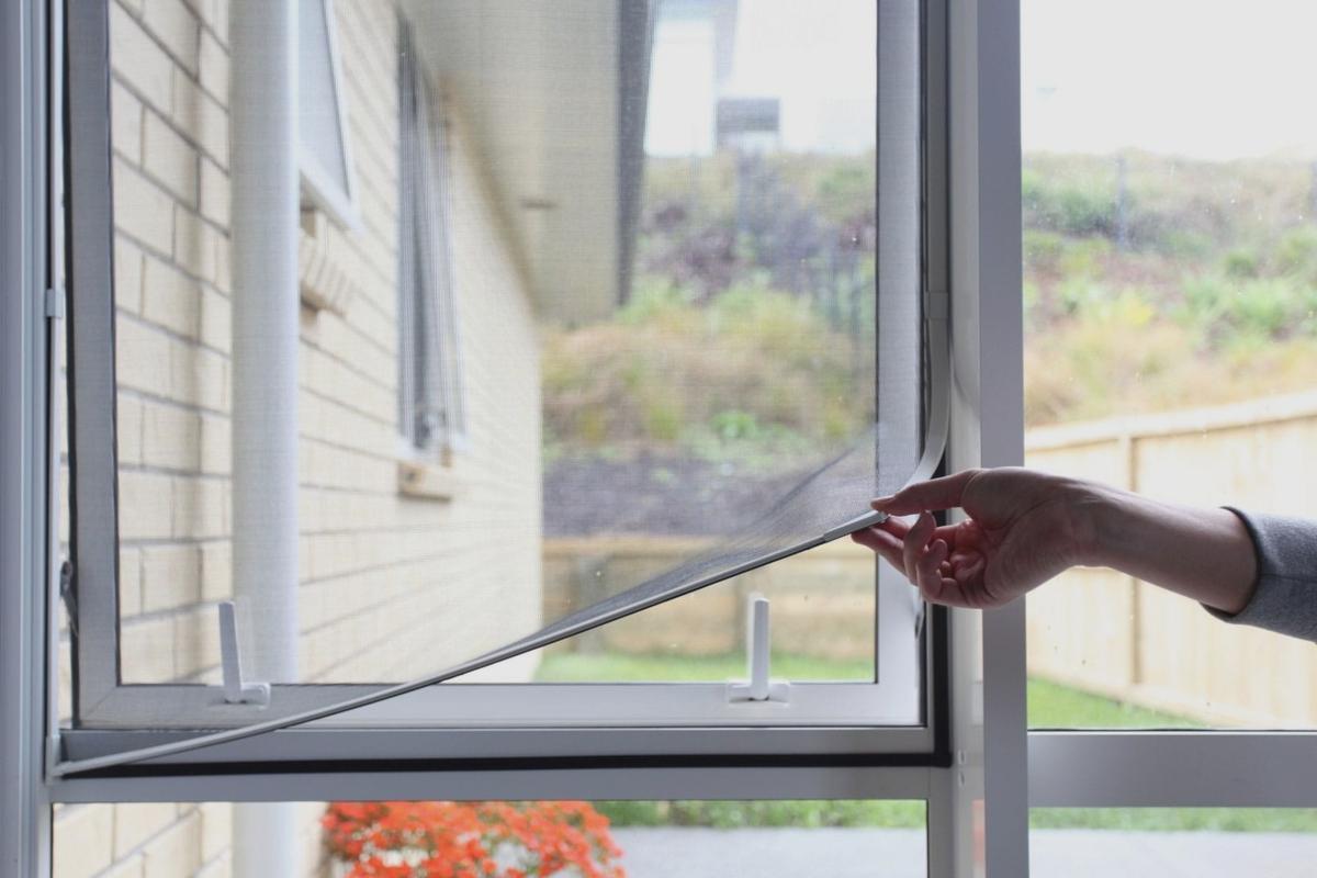 Una persona quitando una mosquitera para limpiarla
